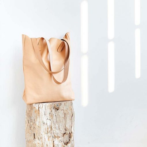 Sustainable leather shopping bag standing on wood